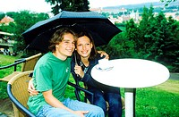 Young couple sitting together under an umbrella