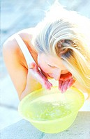 Close-up of a woman washing her face in a basin