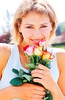 Portrait of a young woman holding roses (thumbnail)