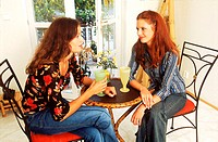 Two young woman sitting together having a drink