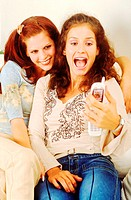 Two young women sitting on sofa holding a mobile phone (thumbnail)