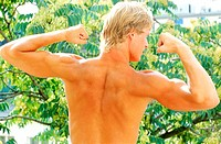 Rear view of young man flexing biceps (thumbnail)