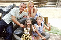 Portrait of a family sitting on a sculpture smiling (thumbnail)