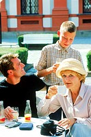 Grandmother and father with young boy on a table outdoors