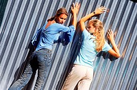 Rear view of two young women leaning against a corrugated metal wall