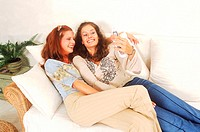 Two young women playing with a mobile phone (thumbnail)
