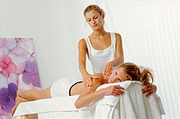 Young woman getting a massage from a masseuse