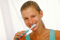 Portrait of young woman brushing her teeth