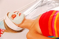 Young woman lying with a face pack