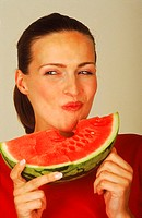 Young woman eating a slice of watermelon