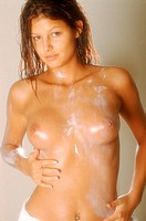 Portrait of a topless young woman applying body lotion
