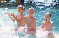 Three children playing in a pool (thumbnail)