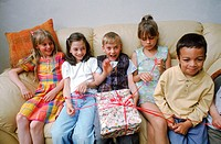 Children sitting on a couch at a birthday party