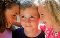 Close-up of a boy standing between two girls
