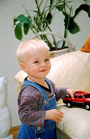 Side profile of a baby holding a toy car