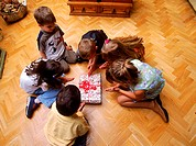 High angle view of kids sitting around a gift