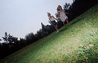 Low angle view of two young girls running in a park
