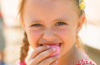 Portrait of a young girl eating candy