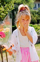 Girl covering her mouth with a bouquet in the other hand