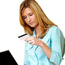 Businesswoman looking at a credit card on front of a laptop