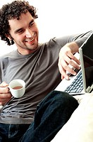 Young man holding a cup of tea using a laptop