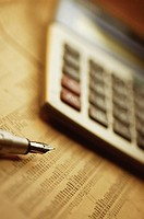 Close-up of a pen and a calculator on a financial newspaper