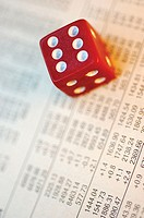 Close-up of a dice on a financial page