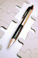 Close-up of a pen with a jigsaw puzzle