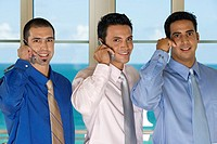 Portrait of three businessmen using mobile phones