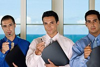 Portrait of three businessmen holding pens