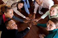 High angle view of a group of business executives with their hands on a table