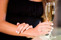Mid section view of a young woman holding a champagne flute (thumbnail)
