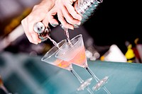 Close-up of a person's hand preparing a cocktail