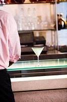 Mid section view of a businessman standing at a bar counter (thumbnail)