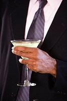 Mid section view of a businessman holding a glass of martini