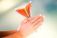 Close-up of a woman's hand holding a glass of martini