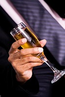 Mid section view of a businessman holding a champagne flute
