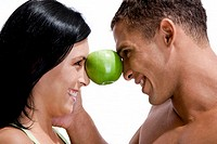 Side profile of a young couple balancing a green apple between their faces
