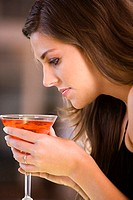 Side profile of a young woman holding a glass of martini