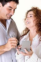 Close-up of a young woman and a mid adult man using a calculator