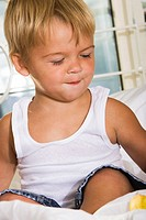 Close-up of a boy sitting on the bed (thumbnail)