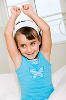 Close-up of a girl smiling with her arms raised