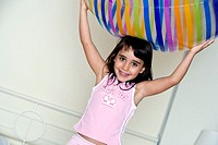 Close-up of a girl holding a large inflatable ball over her head