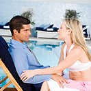 Young woman and a mid adult man sitting at the poolside