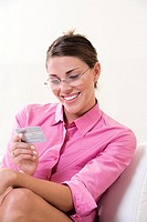 Close-up of a young woman looking at a credit card