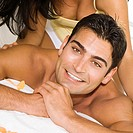 Mid adult woman massaging a mid adult man´s shoulders on the bed