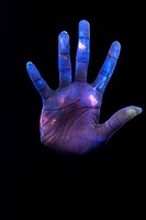 Bacteria on skin. Conceptual image taken in ultraviolet light of a woman´s hand covered in bacteria. Many types of bacteria are found on human skin. M...
