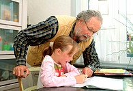 Grandfather helping his granddaughter with her homework.