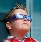 Watching solar eclipse. Young boy using a special protective viewer to observe a solar eclipse. The Sun is seen reflected in the material covering his...