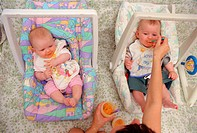 Mother feeding twin babies while they sit in their carry cots,
